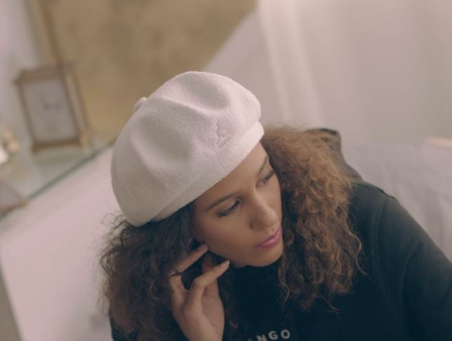 A model wearing a Kangol beret and hoodie